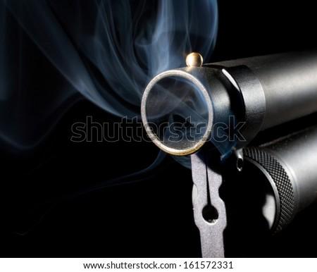 Smoke rising from the barrel of a black shotgun - stock photo