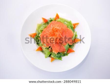Smoke salmon caesar on white plate - stock photo