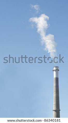 Smoke Stack on a Clear Blue Sky with Smoke. - stock photo