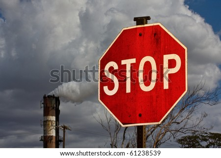 Smoke stack with STOP sign in foreground - environmental concept - stock photo