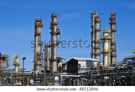 Smoke stacks at oil refinery against blue sky.