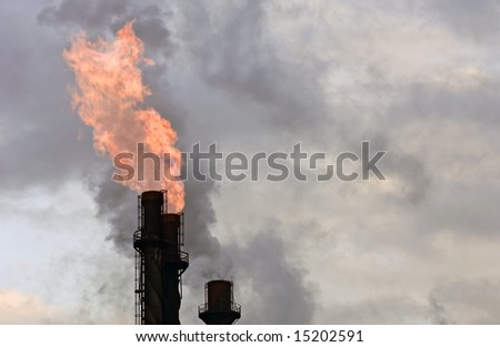 Smoke stacks, equipped with burners to incinerate flammable gases, emitted from a factory against a turbulent sky