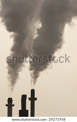 Smoke stacks pumping out pollution in golden evening light.