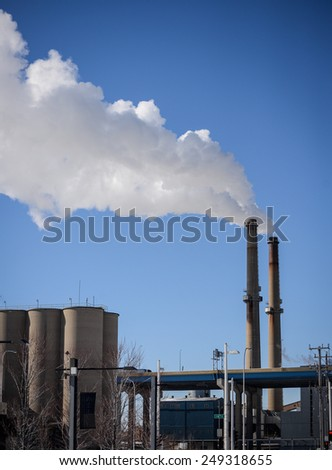 Smoke stacks with white billowing smoke against blue sky