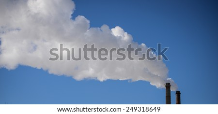 Smoke stacks with white smoke against blue sky