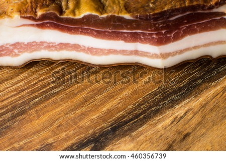 Smoked Bacon on Vintage Wooden Board - stock photo