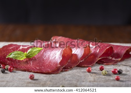 Smoked beef meat slices over rustic background