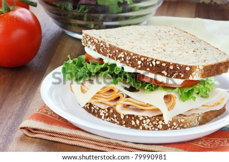 Smoked chicken or turkey sandwich with lettuce, tomato and swiss cheese and whole grain bread. - stock photo