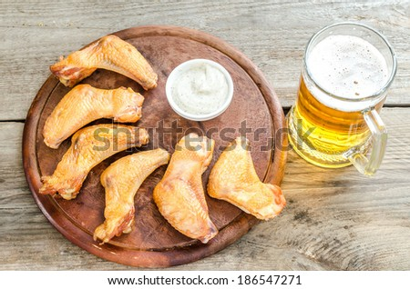 Smoked chicken wings with spicy sauce and glass of beer - stock photo