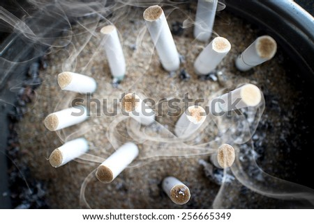 smoked cigarettes butts in a dirty ashtray big bin life concept - stock photo