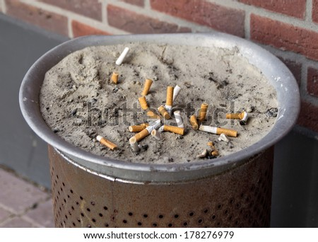 Smoked cigarettes in a dirty ashtray with sand.