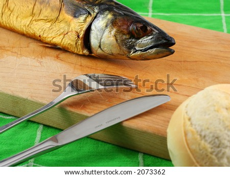 smoked fish on a cutting board with bread and cuttlery - stock photo