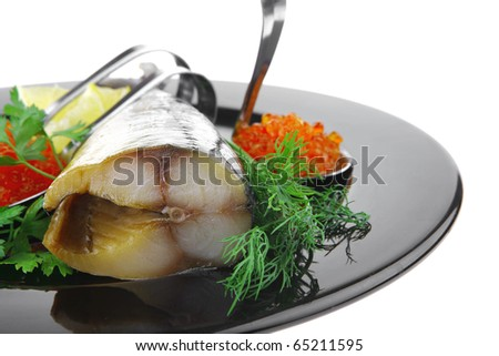 smoked fish with red caviar on black plate - stock photo