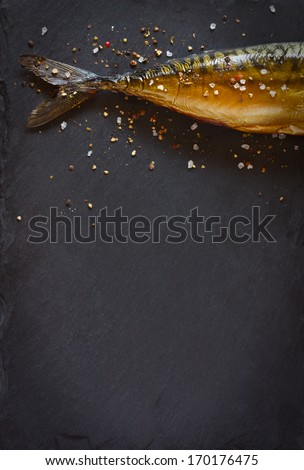 Smoked fish with spices on a black background. - stock photo