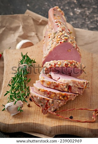 Smoked ham on a cutting board with herbs - stock photo
