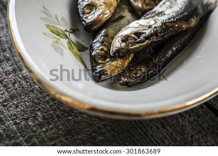 Smoked herring on a white plate on old weathered wooden table