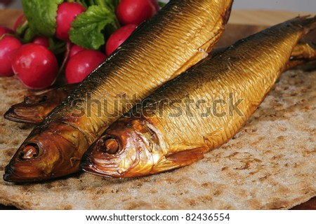 Smoked herring on crispbread, decorated with radishes. - stock photo