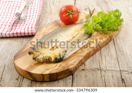 smoked kipper with tomato and parsley on a wooden board - stock photo
