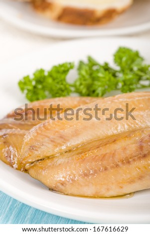 Smoked Kippers - Butterfly smoked herring served with bread. - stock photo