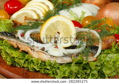 Smoked mackerel fillet with salad, lemon, onions, tomato, garnished with dill on a wooden kitchen board - stock photo