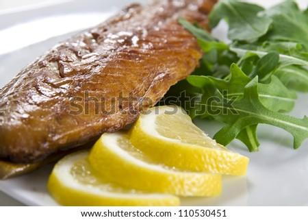 Smoked mackerel fish with lemon and salad - stock photo