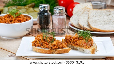 Smoked mackerel pate with herbs, tomatoes and rice on bowl, pickled cucumber, selective focus, square, on wood table. slice of fish pate  - stock photo