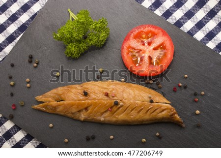 smoked mackerel with a slice tomato, parsley and mixed peppercorn on a slate plate
