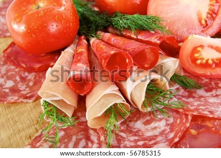 Smoked meat and salami on a wooden board - stock photo