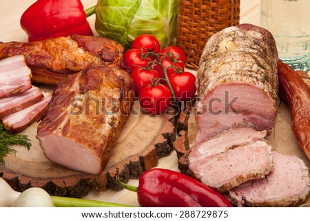 Smoked meat raw bacon with vegetables and salad on wooden background