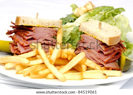 Smoked meat sandwich with fries and Cesar salad - stock photo