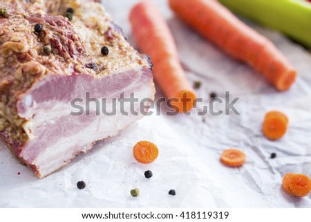 Smoked Meat with Vegetables on Brown Wooden Table. Smoked Raw Layered Meat with Raw Cabbage, Green and Red Peppers, Carrots, Sunflower Oil prepared for cooking. - stock photo