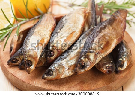 Smoked or dried fish on wooden board - stock photo