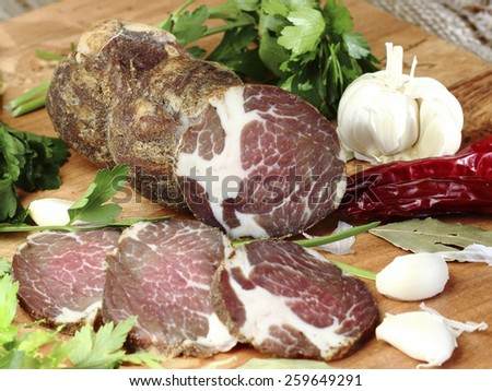 Smoked pork neck with greenery and slices of of garlic on wooden desk - stock photo