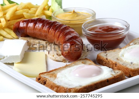smoked pork sausage grilled on a white plate with a nice toast bread and baked egg and two kinds of cheese with fries and lettuce and red tomato ketchup and yellow mustard - stock photo