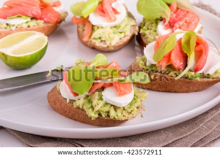 Smoked Salmon and Avocado Open-Faced Sandwich. Smoked Salmon Sandwich with Mozzarella. Smoked Salmon Appetizers. - stock photo