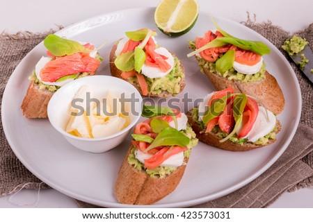 Smoked Salmon and Avocado Open-Faced Sandwich. Smoked Salmon Sandwich with Mozzarella. Smoked Salmon Appetizers. Avocado and Smoked Salmon Crostini. - stock photo