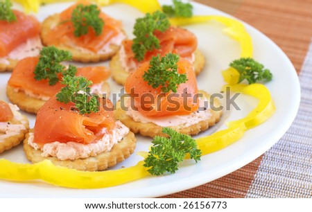Smoked salmon and cream cheese on mini crackers with freshly cracked black pepper and garnishing of parsley