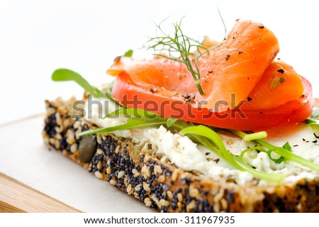 Smoked salmon and salad on a slice of toasted wholewheat bread, a light meal option - stock photo