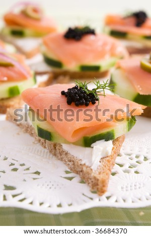 Smoked salmon canapes on rye bread with cream cheese, cucumber, black caviar, and fresh dill. - stock photo
