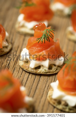 Smoked Salmon Canapes with sprigs of dill and cream cheese on a wooden board - stock photo