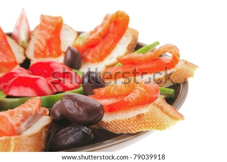 smoked salmon on baguette with olives and pepper . shallow dof