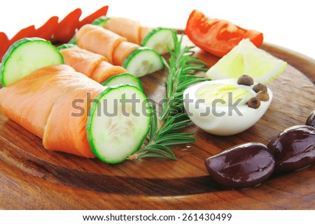 smoked salmon on dark wood with hot peppers - stock photo