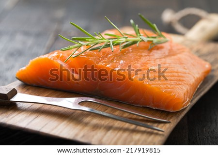 smoked salmon on wooden board - stock photo