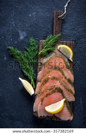 Smoked salmon on wooden board with dill and lemon from above - stock photo