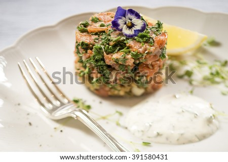 Smoked Salmon, Parsley and Quinoa Cake with a Lemon and Dill Sauce, with a Lemon Wedge on a White Plate - stock photo