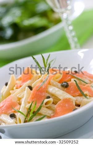 Smoked Salmon Penne (tube-shaped pasta) with cappers, tarragon and cheese creamy sauce. Caesar salad and glass of white wine out of focus. Shallow DOF