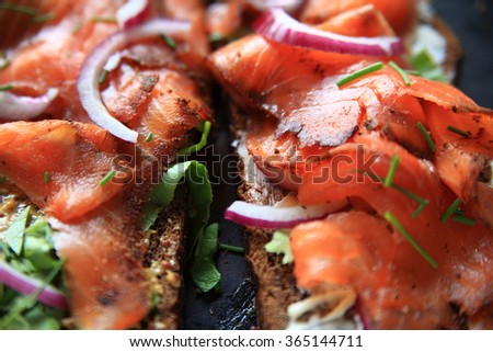 Smoked salmon, red onion, chives and lettuce on dark bread with grainy mustard