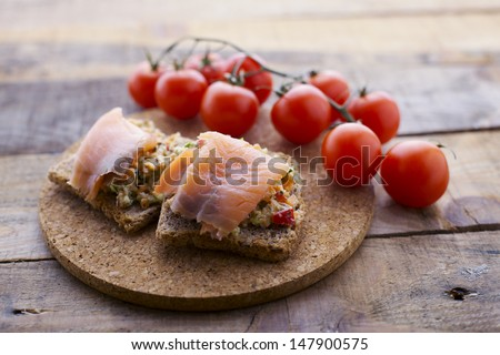 Smoked salmon toast with vegetable coating and cherry tomato. Shallow depth of field. - stock photo