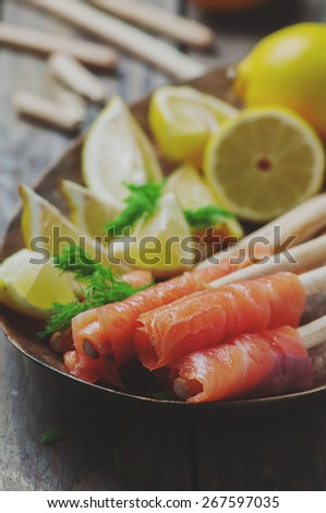 Smoked salmon with grissini and lemon, selective focus and toned images - stock photo
