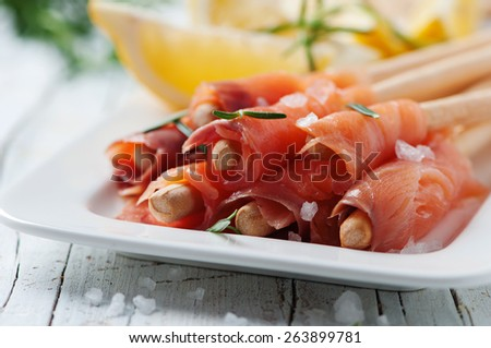 Smoked salmon with lemon and rosemary, selective focus - stock photo